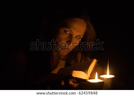 The girl reads the book at candles