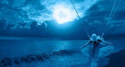 The girl riding a swing on the beach on a full moon at night