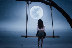 The girl riding a swing on the beach on a full moon night
