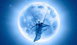 The girl riding a swing on the space on a full moon at night