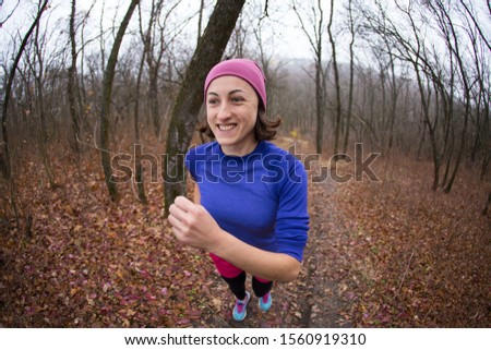 The girl runs through the autumn forest. A woman is training in nature. Runner is preparing for the marathon. Endurance. Sportswear for jogging in the cold season.