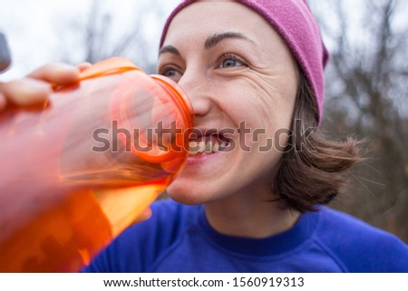 The girl runs through the autumn forest. A woman is training in nature. Runner is preparing for the marathon. Endurance. Girl drinks water after jogging. Sportswear for jogging in the cold season.