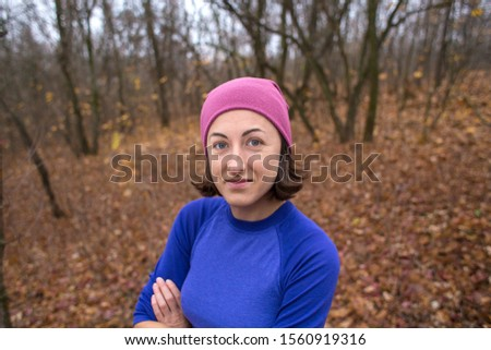 The girl runs through the autumn forest. A woman is training in nature. Runner is preparing for the marathon. Endurance. Girl after jogging. Sportswear for jogging in the cold season.