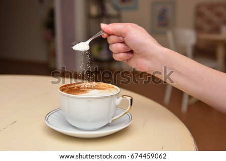 The girl's hand pours sugar into her coffee