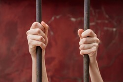 The girl's hands gripped the metal bars. Symbol of violation of women's rights