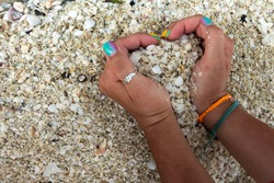 the girl's hands with a beautiful manicure, with ring on her finger and baubles (fandangle, Sequin bracelet, friendship bracelets) on her wrist keeps the sand from the shells in the shape of heart