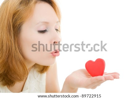 The girl sends an air kiss in the form of heart on a white background.