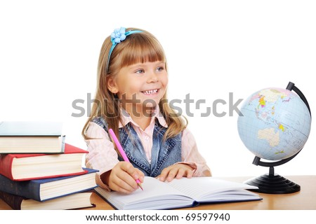 The girl sits at a table and writes to writing-books. Globe on table. Photo Isolated over white