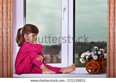 The girl sits at a window