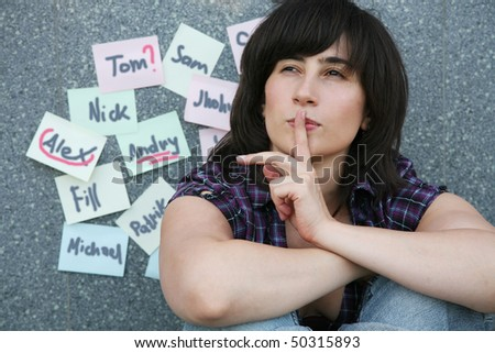 The girl sits before the sheets attached on a wall with names of guys. She thinks whom from them to choose