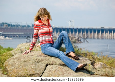 The girl sits on stones against hydroelectric power station. Zaporozhye. Ukraine - stock photo