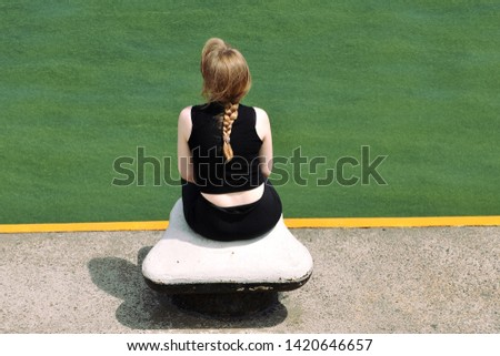 The girl sits on the bollard of sea berth and observes sea flowering which is coloured green #1420646657