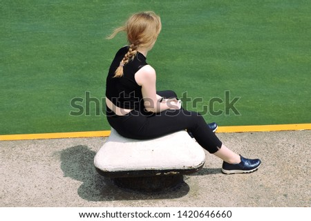 The girl sits on the bollard of sea berth and observes sea flowering which is coloured green #1420646660