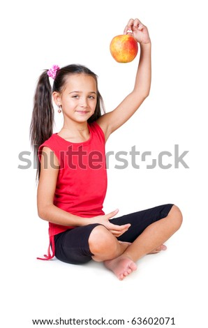 The girl sits with an apple on a white background