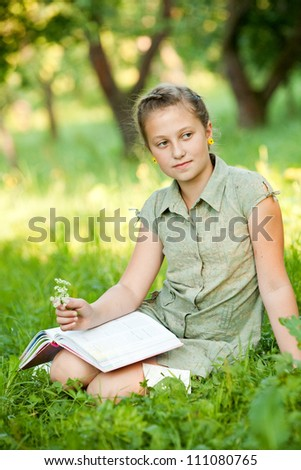 The girl sitting on a grass with a book holding flowers, looking away