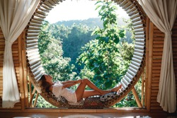 The girl sitting on the indow in the morning in the wooden bamboo house, enjoy tropical vacation on Bali island. Attractive girl sit on open-air veranda of wooden bungalow with tropical garden view