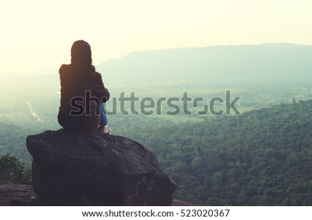 The girl sitting on the rock mountain , relaxing on the top of the mountain, silhouette