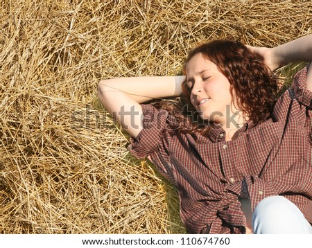 The girl sleeps on a haystack