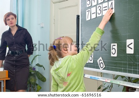 The girl solves an example at a board,