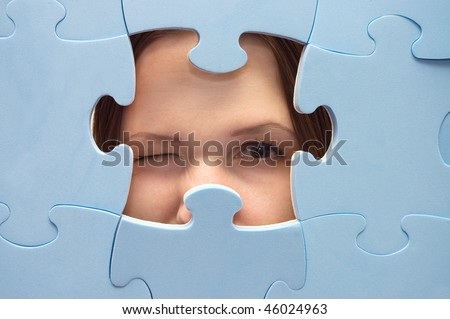 The girl spies through a blue puzzle