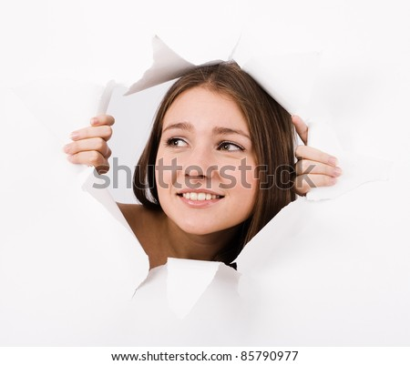 The girl spies through a hole in a paper.