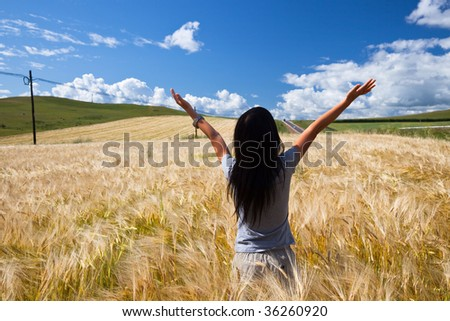 the girl stand in the wheaten field.