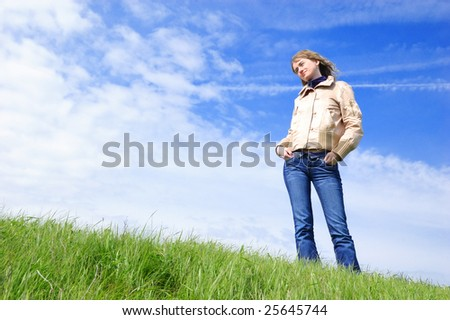 The girl stands in the field and looks afar