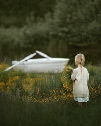 The girl stands with her back to the white boat by the river. In front of the boat is a clearing of the same colors. Image with selective focus.