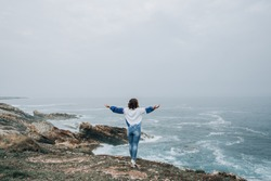 The girl stands with her back turned against the background of the Seascape at the cliff of the mountain, large strong waves, a storm warning in a yoga pose with her arms outstretched to the side