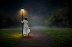 The girl stood alone on the gazebos on the dirt road in the night.