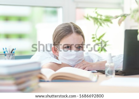 The girl studies at home in a protective face mask during Quarantine CoVid-19. She is tired of studying at home. Distance learning online with a laptop. The child is doing homework for school. The sch Stock foto ©
