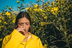 The girl suffers from pollen allergy during flowering and uses napkins. Young woman got nose allergy, flu sneezing nose. Woman is blowing her nose near flowers in bloom. Allergy