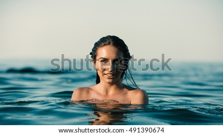 the girl swims in the sea. she very interestingly looks at us. her shoulders look out of water. the sun gently falls her on the person.