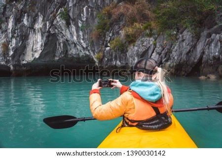 The girl takes a picture of a beautiful landscape sitting in a kayak.. kayaking tour of the islands, a holiday in Asia, a kayak's nose on the water. photograps in the boat.