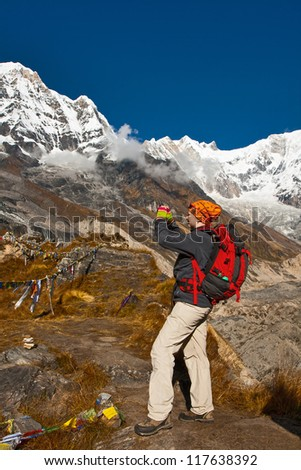 The girl takes photo of mountains in Annapurna Base Camp