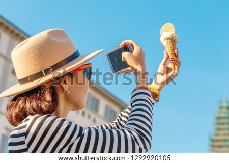 The girl takes pictures of ice cream on her smartphone