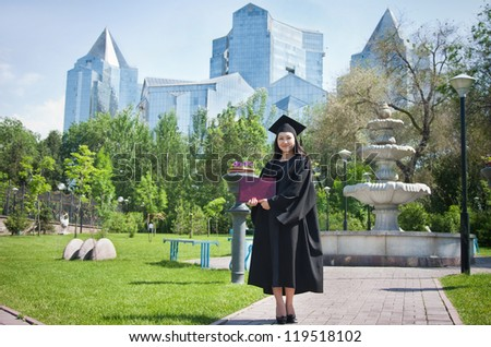 The girl the graduate of university with the diploma in hands, in park