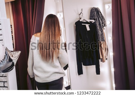 The girl, the seller helps the customer to choose clothes in the try on room in the store.