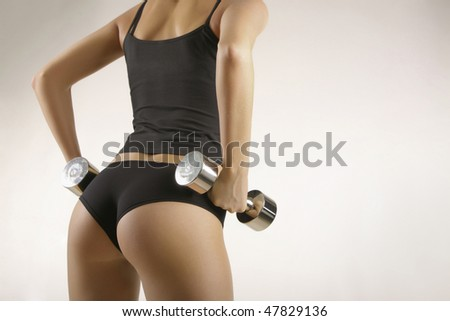 The girl the sportswoman with dumbbells