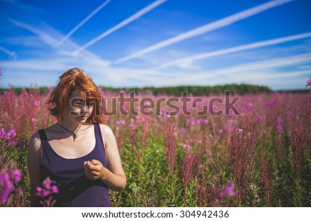 The girl thinking on the middle of the field of Chamaenerion with lines cloud on sky