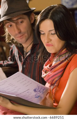 The girl thumbs through the menu at restaurant. On a background its boyfriend.