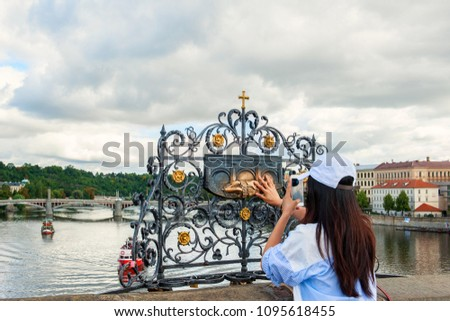 The girl touches the statue of St. John Nepomuk on Charles bridge Prague. The touch of a person to the memorial plaque of the Saint should bring good luck and ensure your well-being #1095618455