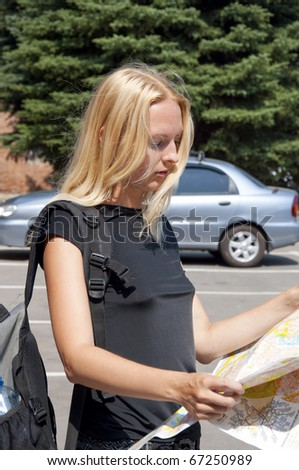 The girl-traveler with a map of the city and a backpack - stock photo