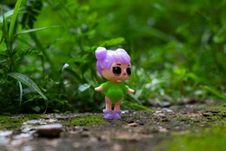 The girl type toy is in the park. Natural background
