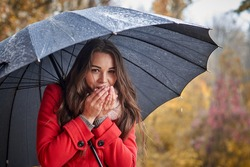 The girl under the umbrella warms her hands with her breath