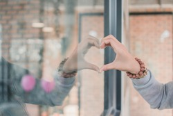 The girl used her hand to make a heart symbol on the surface of the glass in a coffee shop while she went to sit and drink coffee in the morning to show the symbol of love, friendship and compassion.
