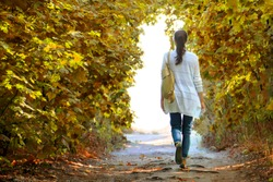 The girl walks along the path in the autumn woods to the light in a white jacket and jeans.