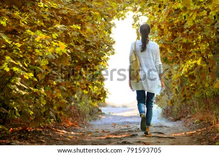 The girl walks along the path in the autumn woods to the light in a white jacket and jeans. #791593705