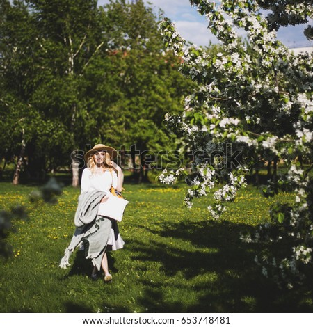 The girl walks in the Park. spring, the Apple trees are blooming #653748481