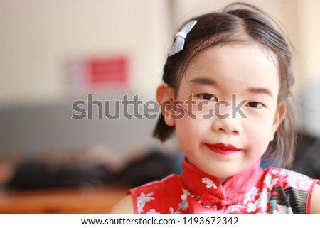 The girl wears the chinese red dress Smiling and bright Cheerful, cheerful, 6-7 years old
